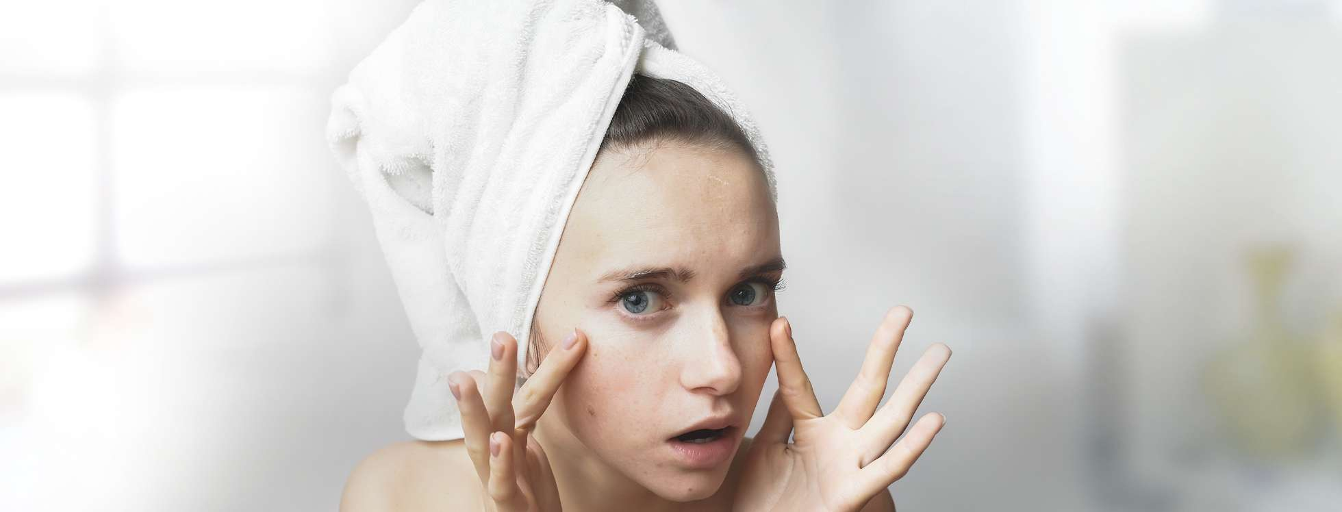Girl looking at her skin in a bathroom mirror with a white towel wrapped around her head