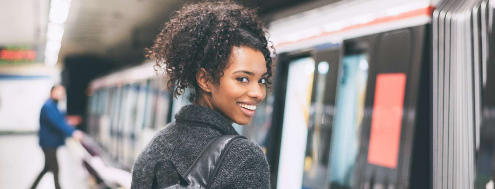 Woman with curly hair looking over her shoulder wearing a backpack on a train platform