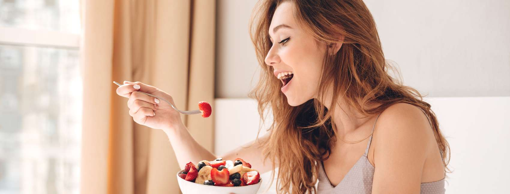 Smiling girl with long hair in a bedroom setting eating a bowl of fruit salad from a fork <br>
