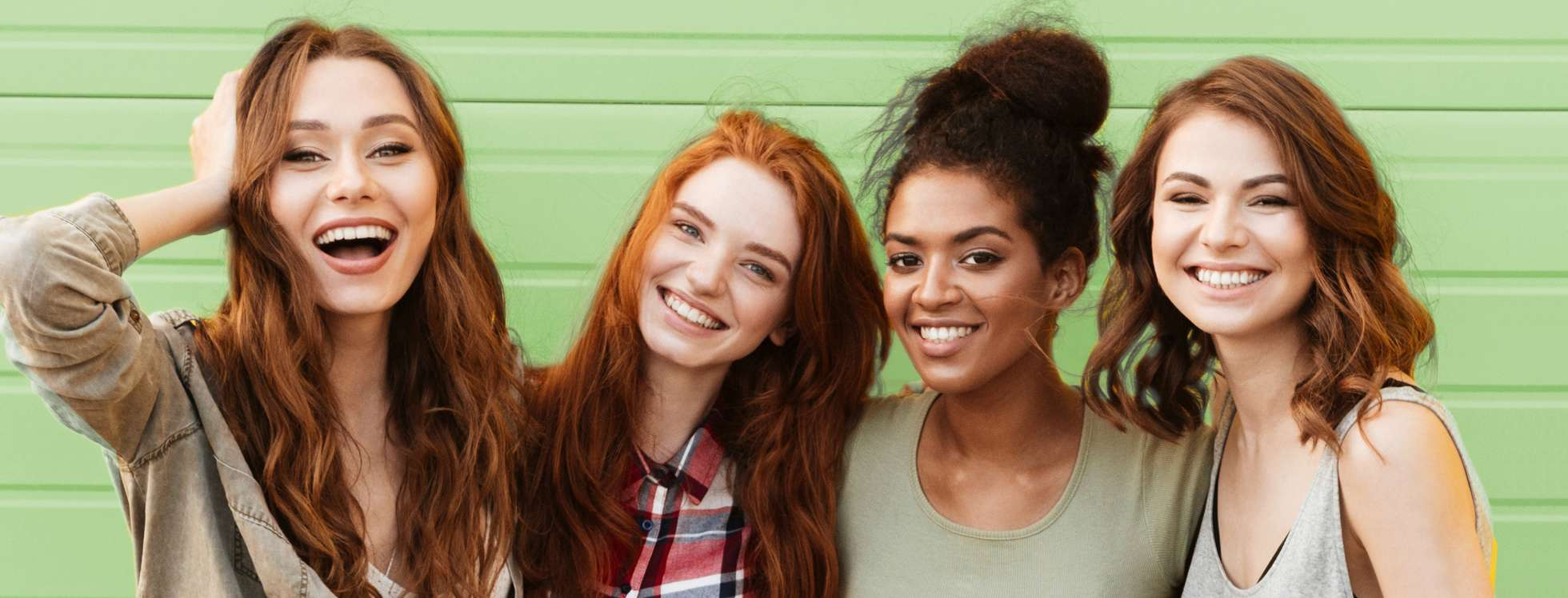 Four smiling girls in front of a green background