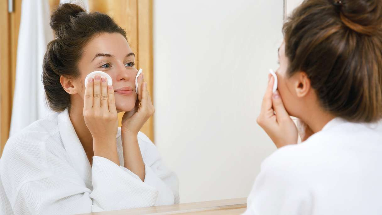 Woman washing her face using two cotton pads