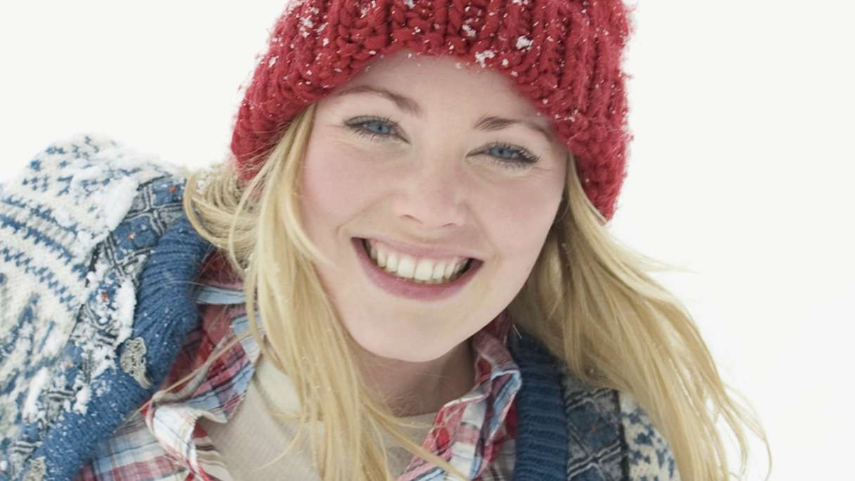 Smiling woman wearing a red beanie in the snow