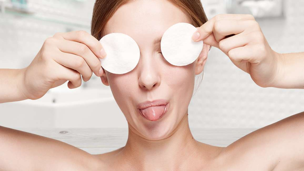 A woman holding cotton pads over her eyes in a bathroom setting