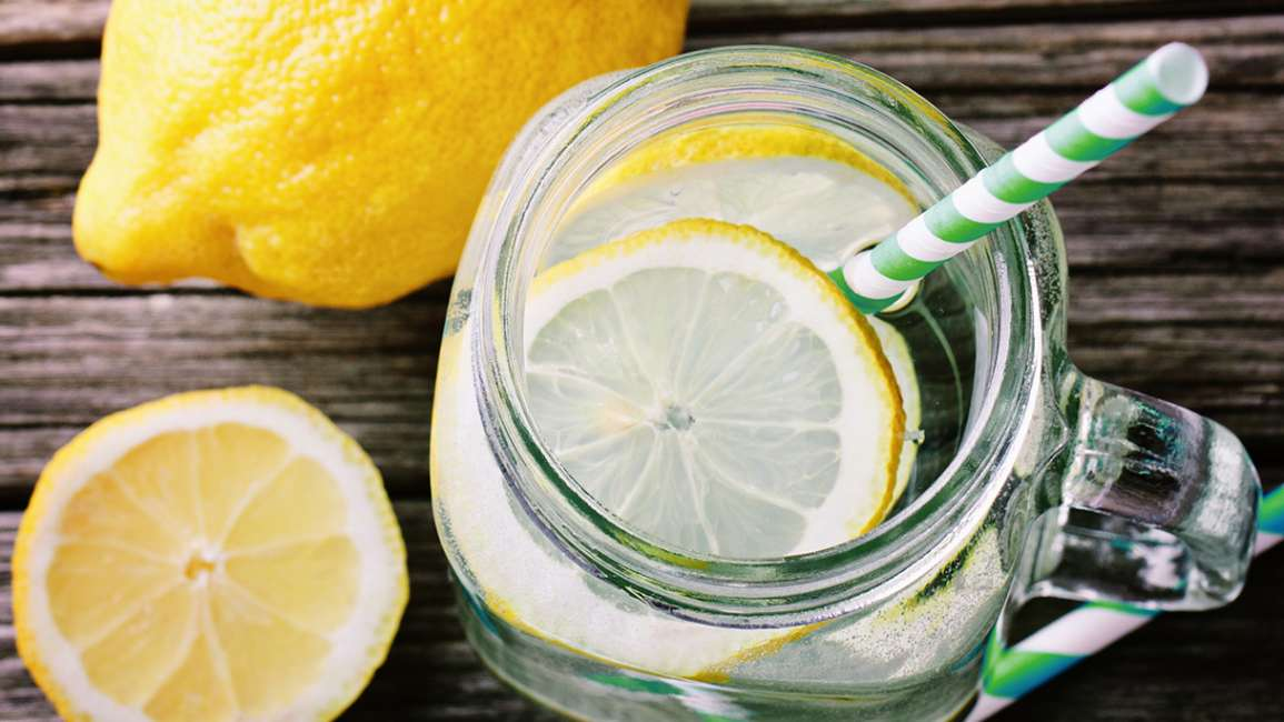 A mason jar full of water with lemon slices and a straw on a wooden table