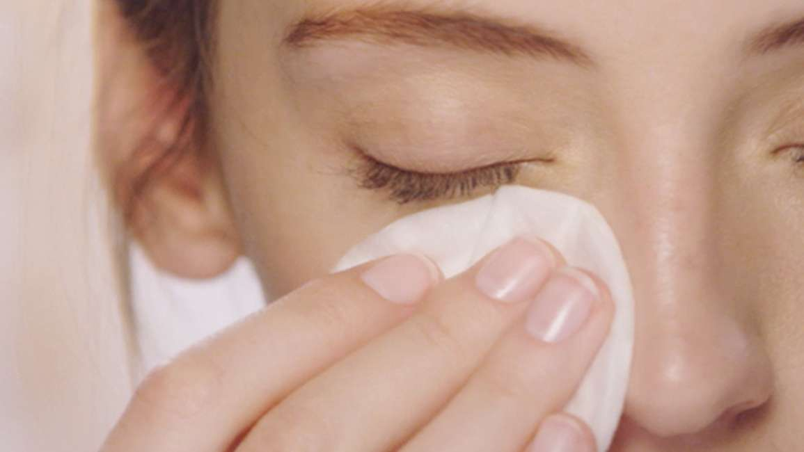 Girl softly using a cotton pad to wipe under her eye