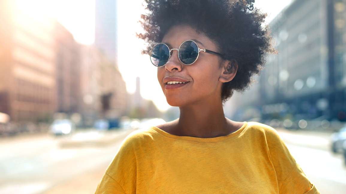 Smiling woman standing on a city street wearing a yellow top and sunglasses