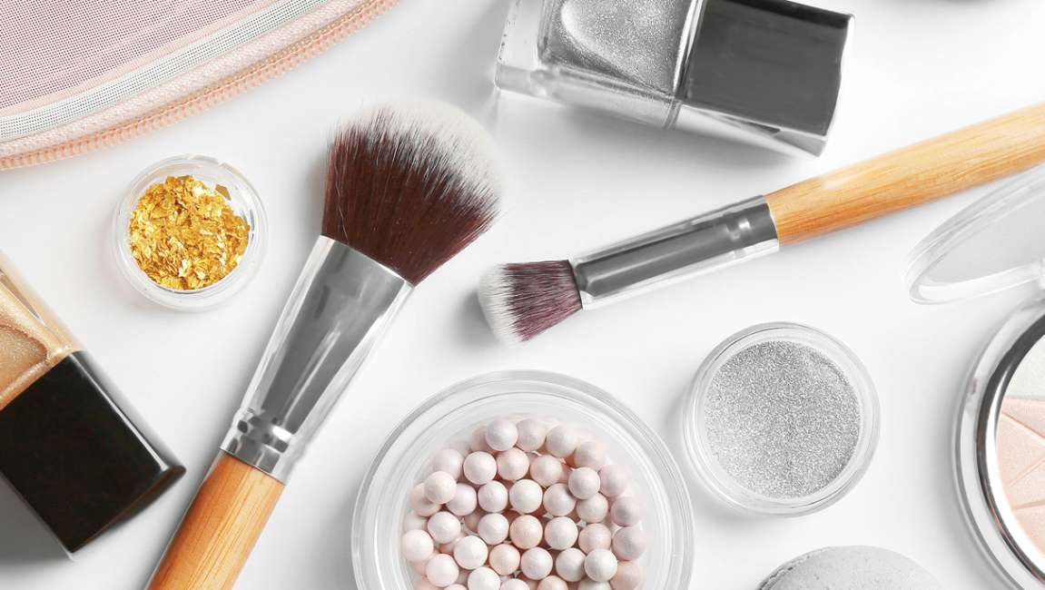 Selection of scattered make-up, powders and brushes