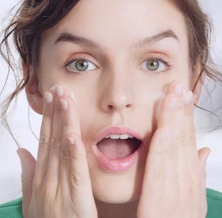 7 tips for soothing sensitive skin green dress hands on her face
