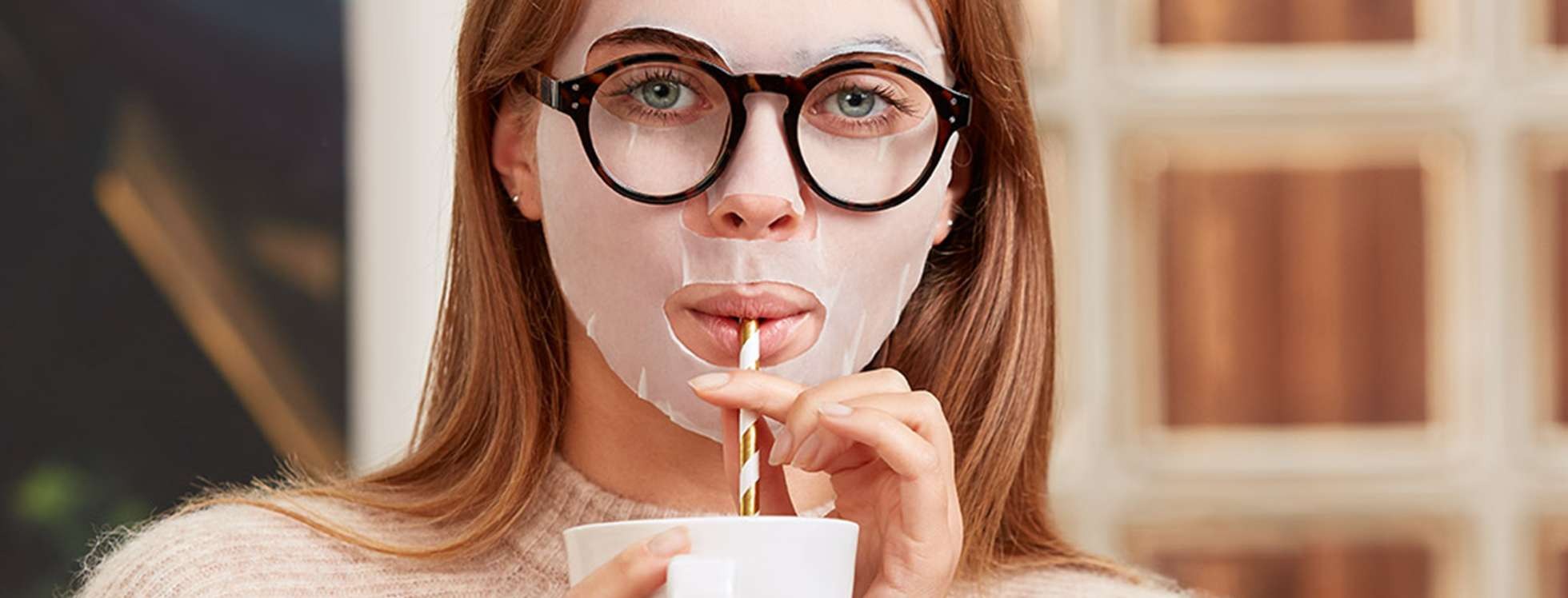 Woman wearing a sheet mask and spectacles