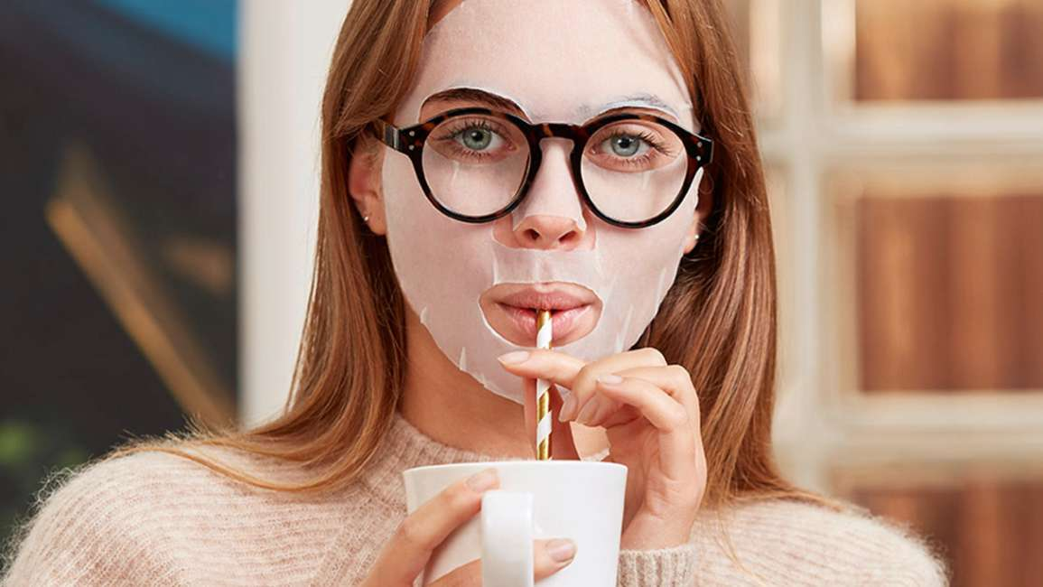 Girl wearing spectacles and a sheet mask drinking through a straw