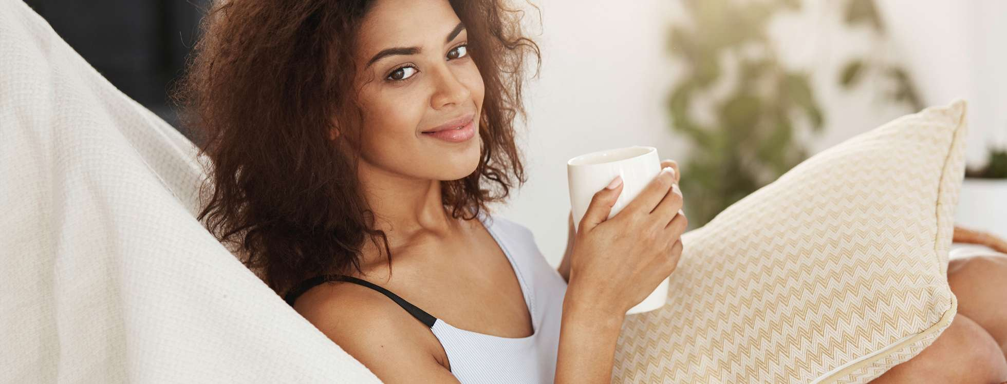 A smiling woman relaxing with a hot drink