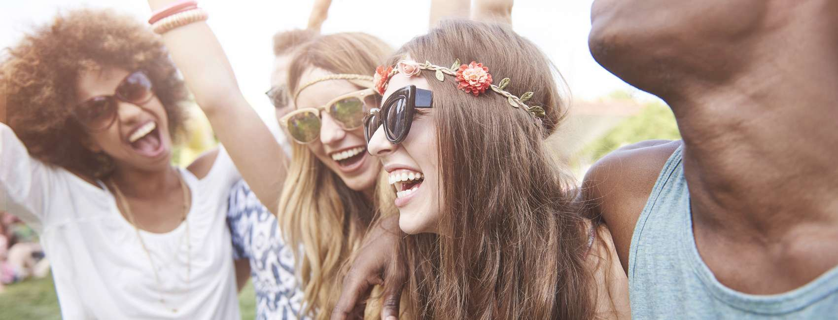 Three smiling girls wearing sunglasses in a festival setting