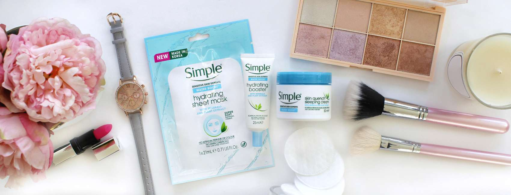 Flat lay of Simple water boost products alongside pink flowers and make-up.