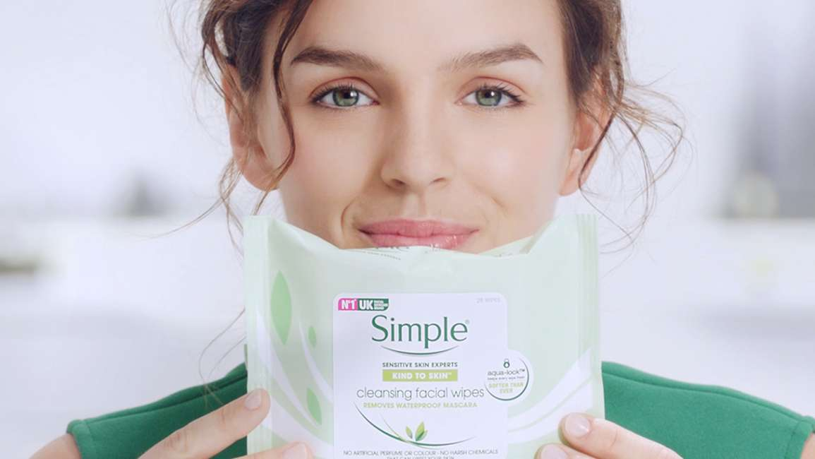 Woman holding up a pack of Simple Facial Cleansing wipes