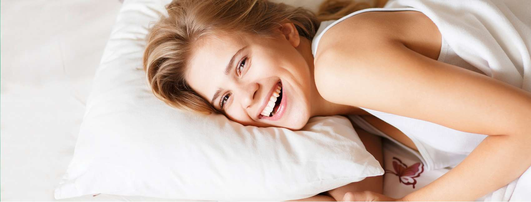 Smiling woman who looks rested is lying in bed