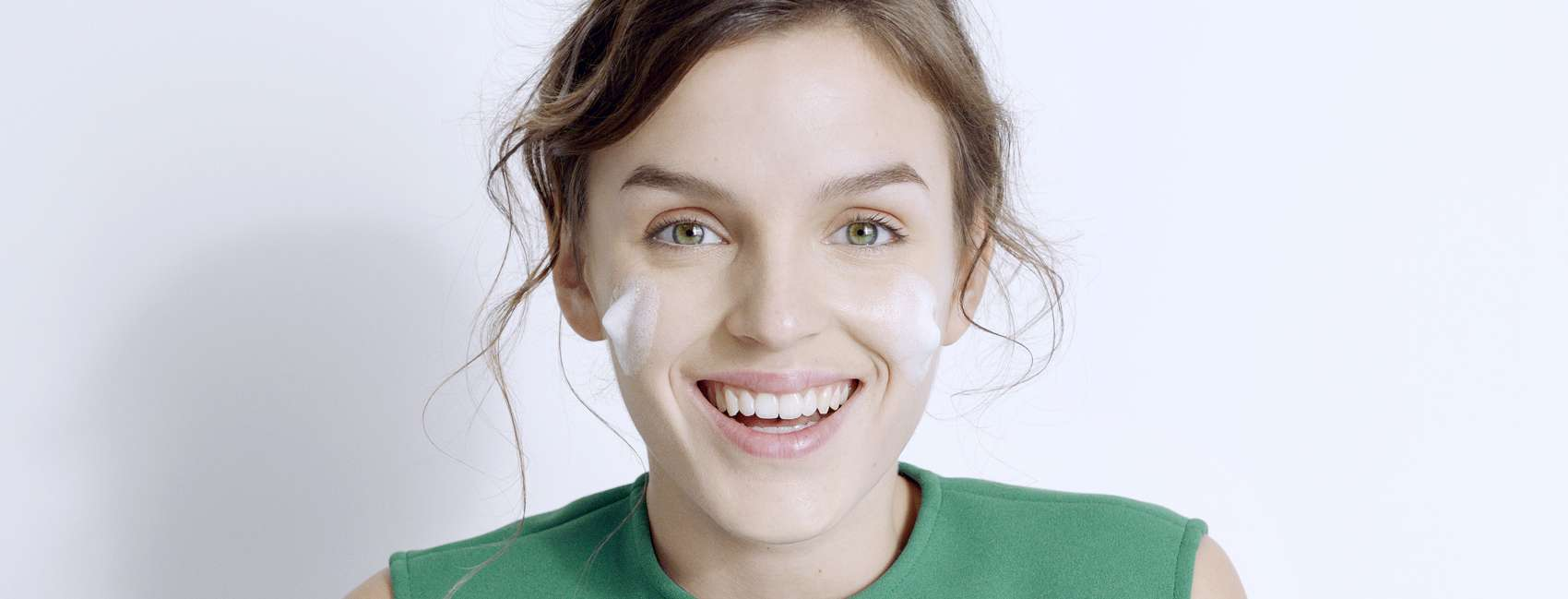 Girl in green dress with foamy face wash on her cheeks