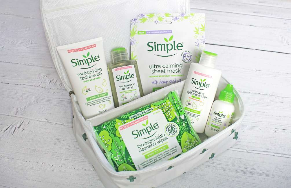 Simple products in a white toiletry bag on a white wooden floor