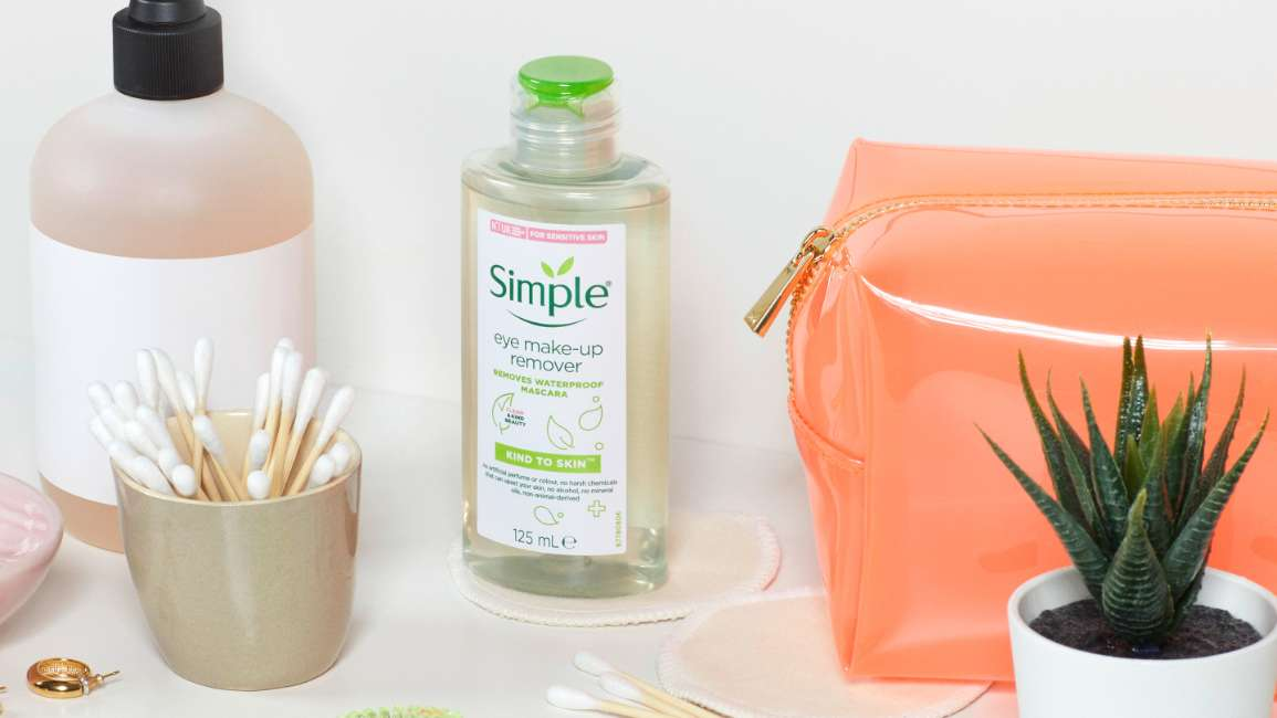 Simple eye make up remover, cotton buds, orange toiletry bag in a bathroom setting